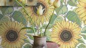 Фото интерьера с обоями в задорном цветочном узоре в желтых, оранжевых, зеленых и синих тонах, белый фон и мягкая текстура ткани: обои Solrosor излучают радостное настроение. Эффектные подсолнухи с сочными листьями, вручную написанные гуашью, наполнят ваш дом теплом и радостью.