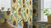 Фото обоев в кабинете. Задорный цветочный узор в желтых, оранжевых, зеленых и синих тонах, белый фон и мягкая текстура ткани: обои Solrosor излучают радостное настроение. Эффектные подсолнухи с сочными листьями, вручную написанные гуашью, наполнят ваш дом теплом и радостью.
